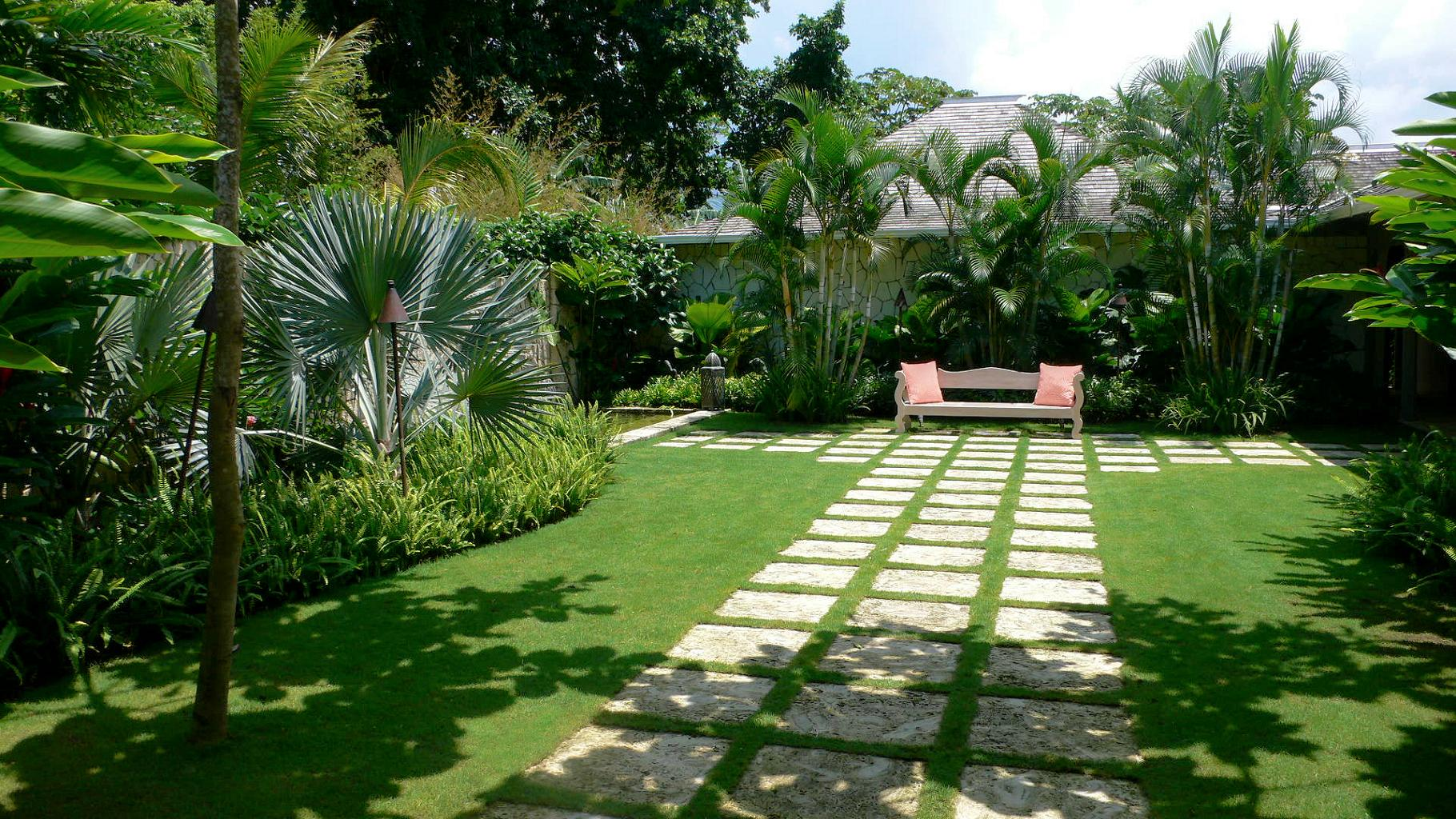 modern-landscape-design-ideas-for-backyard-garden-of-a-house-with-stone-floored-footpath-bench-trees-and-tropical-plants