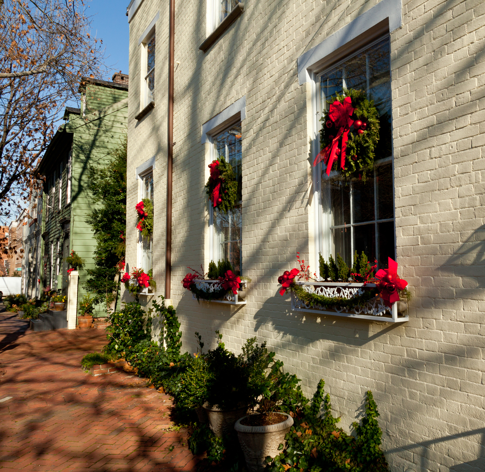 Old brick colonial house decorated for Christmas with wreath on door