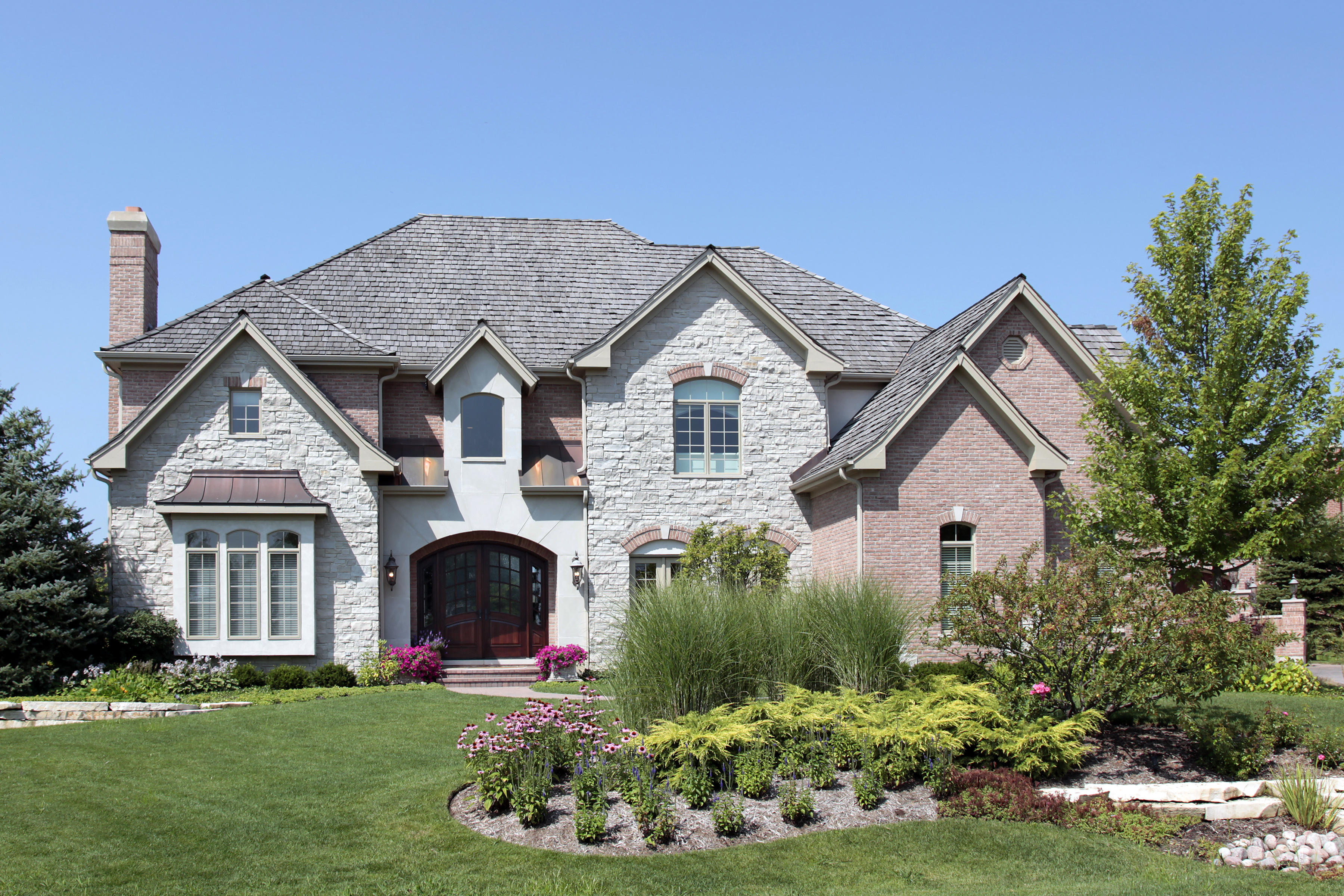 Large stone and brick home with arched doorway