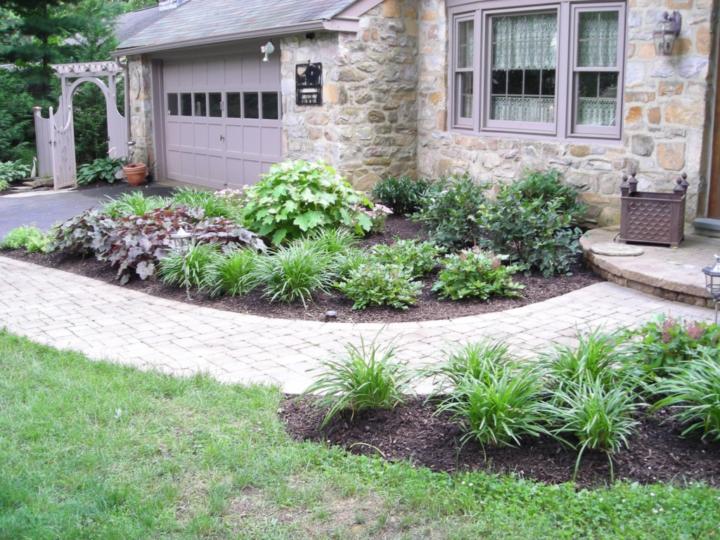 garden-and-patio-rustic-ranch-house-design-with-exterior-exposed-stone-wall-and-small-landscaping-house-design-with-paving-block-walkway-and-small-gardening-with-herb-plants-beside-garag